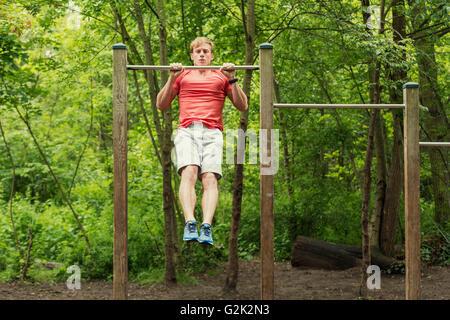 Atleta maschio facendo muscolo-up sulla barra orizzontale Foto Stock