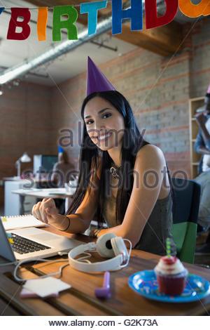 Ritratto sorridente imprenditrice festeggia il compleanno al laptop Foto Stock