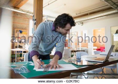 Designer con un righello e bradawl lama sul tappeto di taglio in office Foto Stock