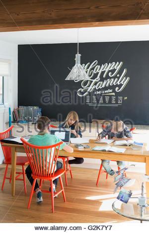 Fratelli e sorelle di fare i compiti al tavolo da pranzo Foto Stock
