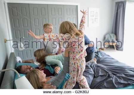 Bambini allegri in pigiama saltando sui genitori nel letto Foto Stock