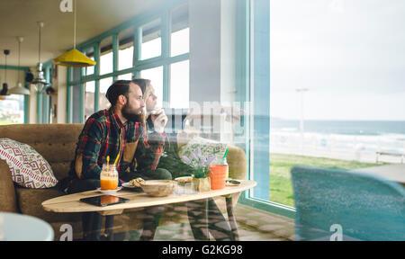 Spagna, Asturias, giovane godendo il seascape attraverso la finestra cafe pur avendo un brunch Foto Stock