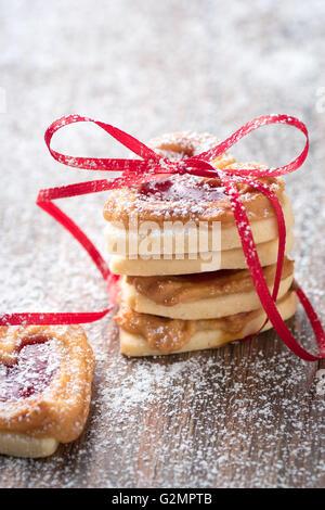 Un mucchio di cuore i cookie su una tavola in legno rustico. È possibile utilizzarlo per un biglietto di auguri o ricetta. Foto Stock