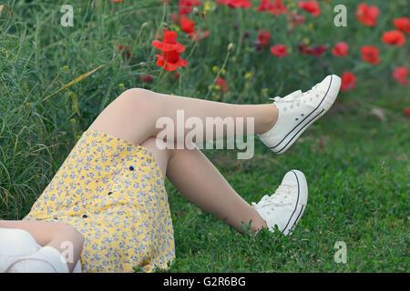 Giovane ragazza distesa sul campo di papavero Foto Stock
