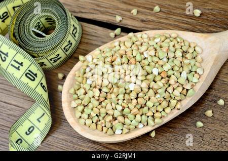 Il verde del grano saraceno in un cucchiaio di legno e centimetro su tavola Foto Stock