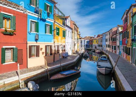 Insolitamente edifici dipinti, barche parcheggiate in canali, la città di Burano. Foto Stock