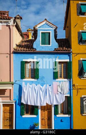 Lavanderia appesi sulle linee nella parte anteriore delle case di Burano. Foto Stock