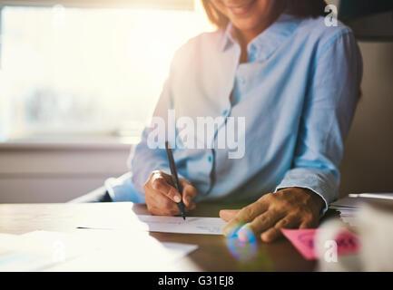 Primo piano delle mani la scrittura sulla busta con una calda luce del sole proveniente attraverso la finestra Foto Stock