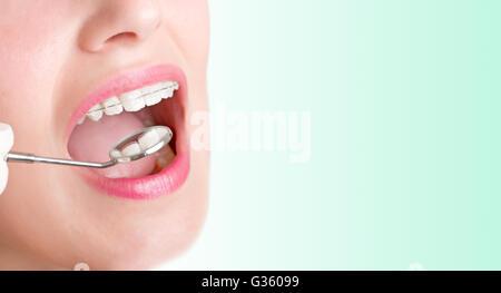 Primo piano di un dentista mani circa per eseguire un intervento su un paziente in uno sfondo verde Foto Stock