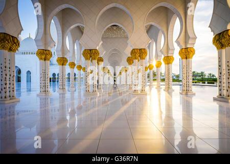 Una vista verso il basso un colonnato in Sheikh Zayed Grande Moschea di Abu Dhabi al tramonto Foto Stock