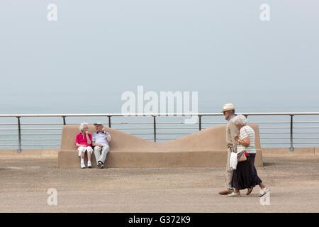 Tempo caldo a Blackpool , Inghilterra.Godersi il caldo sul lungomare.Una coppia di anziani prende una passeggiata Foto Stock