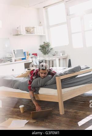 Giovane uomo posa sul letto tramite computer portatile in appartamento Foto Stock