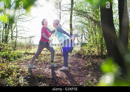 Vista laterale della donna nella foresta faccia a faccia tenendo caviglia gamba di stiramento Foto Stock