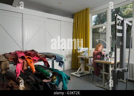 Donna alla macchina da cucire in officina Foto Stock