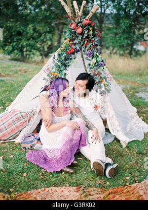 La Svezia, la sposa e lo sposo seduto sul prato di fronte della tenda bianca al matrimonio hippie Foto Stock