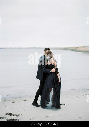 La Svezia, Halland, Varberg, giovani formalmente vestiti giovane camminando lungo la spiaggia Foto Stock
