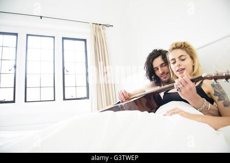 Un giovane tatuato giovane posa su un letto con una chitarra. Foto Stock