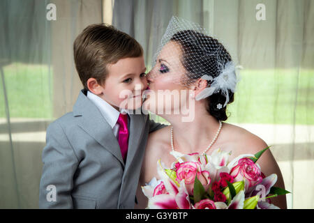 Una giovane sposa bacia il figlio il giorno del matrimonio nella sua pre-ritratto di nozze. Ha conseguito il suo Foto Stock