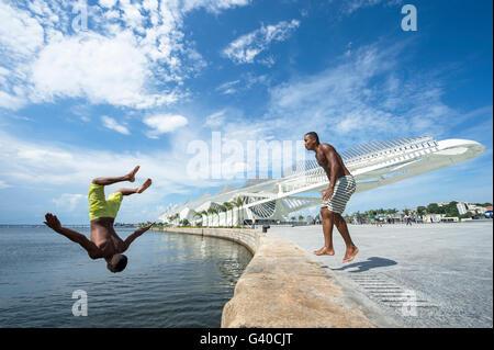 RIO DE JANEIRO - Febbraio 25, 2016: i giovani brasiliani salto nella baia di Guanabara dalla parete di Maua Plaza, Porto Maravilha. Foto Stock