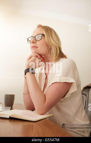 Ritratto di coppia imprenditrice seduto alla sua scrivania e guardando lontano pensando. Femmina caucasica seduto Foto Stock