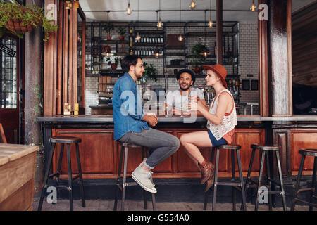 Ritratto di felice gruppo di giovani riuniti in un coffee shop e parlare. Tre giovani amici seduti ad un tavolo Foto Stock