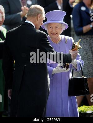 La regina Elisabetta II riceve il trofeo dal duca di Edimburgo dopo che la sua stima del cavallo ha vinto il vaso della regina durante il quarto giorno della riunione reale di Ascot 2012 all'ippodromo di Ascot, Berkshire.