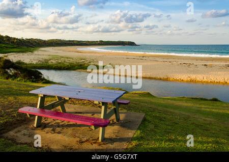 Un vuoto di una panchina nel parco si affaccia una spiaggia nel NSW Mid North Coast in Australia Foto Stock
