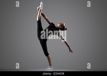 Bella giovane montare ginnasta atleta donna in sportswear, dancing, equilibrio facendo ginnastica ritmica esercizio Foto Stock