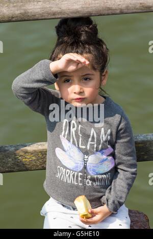 Ragazza giovane schermare gli occhi dal sole, una mela a Bournemouth Pier in giugno Foto Stock