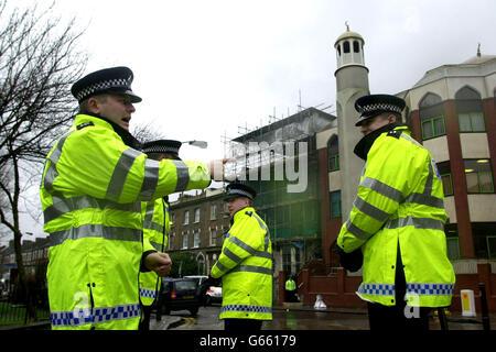 I poliziotti si trovano accanto al cordone di fronte alla Moschea di Finsbury Park, nel nord di Londra, dove la polizia aveva condotto un raid nelle prime ore del 20 gennaio 2003. *..i detective antiterrorismo continuavano a mettere in discussione sette uomini arrestati in un'incursione da più di 100 ufficiali nella moschea. Scotland Yard scoprì una pistola stordente, un'arma d'imitazione che spara gli spazi vuoti e un barattolo di gas CS durante la ricerca. Foto Stock