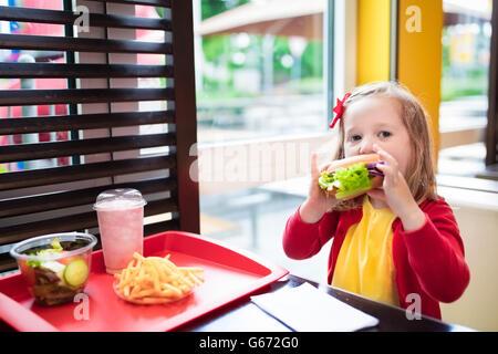 Bambina e ragazzo mangiare Chicken Nuggets, hamburger e patatine fritte in un ristorante fast food. Bambino con Foto Stock