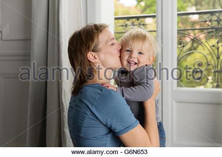 Ritratto di sorriso toddler kissing da sua madre Foto Stock