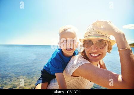 Felice giovane madre e figlio su una spiaggia tropicale con la risata di Little Boy ottenendo un piggy back corsa Foto Stock