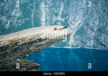 Odda, Norvegia - 04 agosto 2014: il giovane uomo su roccia aggrappato al bordo di una scogliera e guardando verso Foto Stock