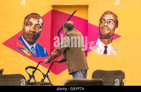 A Las Palmas di Gran Canaria Isole Canarie Spagna, 30 giugno 2016. Un uomo cammina passato una parete dipinta con immagini di Martin Luther King e Malcolm X. i graffiti sul muro di un edificio vacante molti cambiamenti quasi su una base settimanale. Credito: Alan Dawson News/Alamy Live News