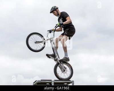 Stunt rider tenendo la sua stunt bike sulla ruota posteriore su una piattaforma elevata Foto Stock
