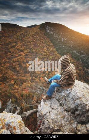 L'uomo in montagna seduto sulla scogliera. Scena concettuale. sulla scogliera. Scena concettuale. Foto Stock