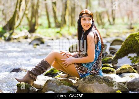 Hippie ragazza in natura rocciosa all'esterno guardando indietro sulla spalla attraente seduta seduto su roccia Foto Stock