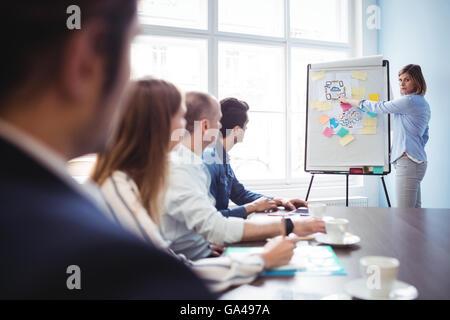 Imprenditrice dando una presentazione in sala riunioni Foto Stock