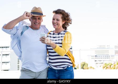 Felice coppia utilizzando un cellulare in città Foto Stock