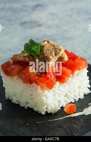 Riso bianco con pomodoro e tonno su piastra in piastrelle nere Foto Stock