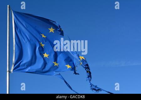 L'Unione europea dodici stelle bandiera strappata e con nodi di vento sul cielo blu Foto Stock
