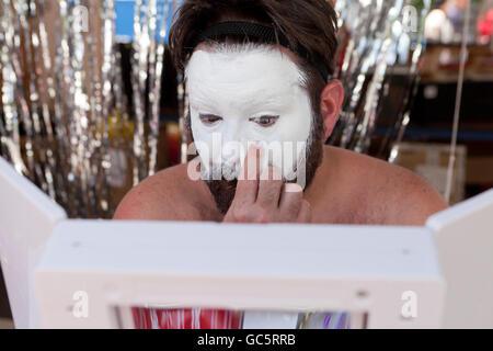 Applicando l'uomo bianco base trucco sulla faccia - USA Foto Stock