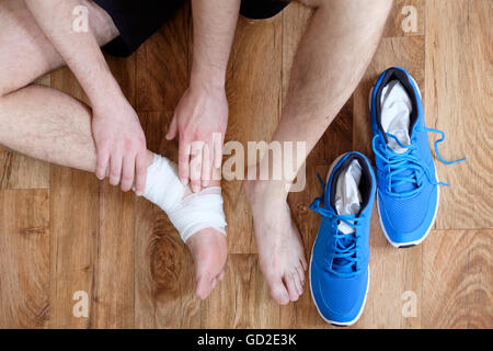 Massaggio sportivo la sua caviglia infortunata dopo un incidente di sport Foto Stock
