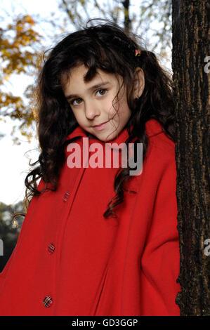 Bambina di cinque anni in rosso cappotto in piedi vicino a un albero in un parco Foto Stock
