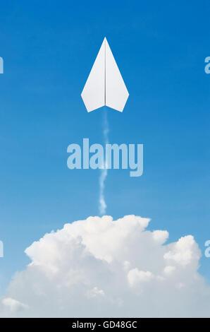 Aeroplano di carta battenti alto sopra le nubi con cielo blu. Foto Stock