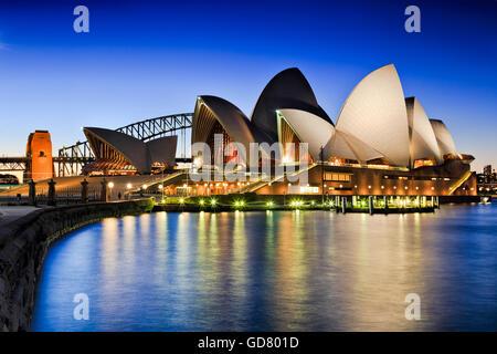 SYDNEY, AUSTRALIA, 1 luglio 2016 - Sydney Opera House e Harbour Bridge al tramonto che riflette le luci nella baia sfocata