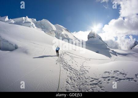 Uomo che cammina sul ghiacciaio delle Alpi svizzere, il Piz Bernina, Grigioni, Svizzera Foto Stock