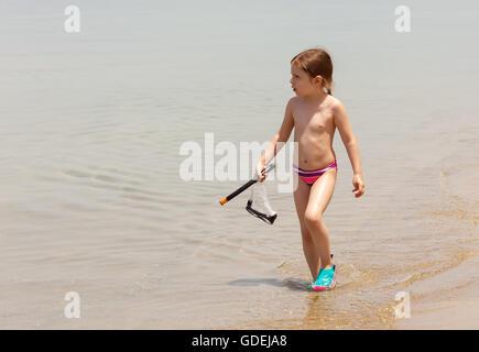 Ragazza camminare al di fuori del mare portando, fare snorkeling e maschera Foto Stock