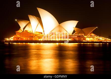 Accesa la Opera House di Sydney si riflette nell'acqua del porto. Foto Stock